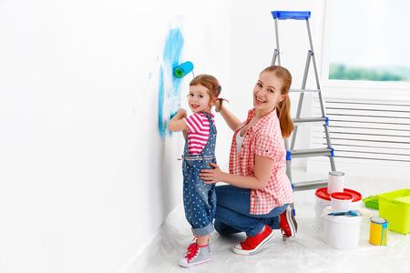 felice madre e figlia famiglia bambino che fa le riparazioni, dipingere il muro a casa Archivio Fotografico