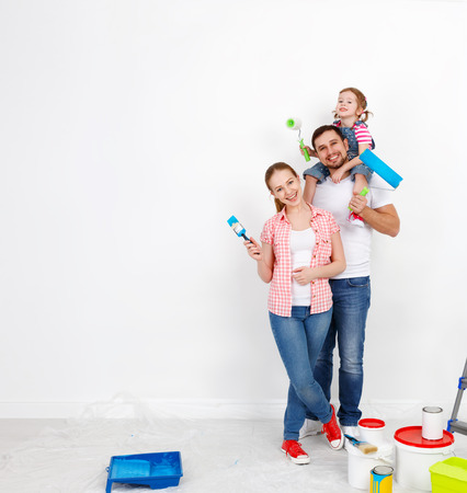 dad and daughter: happy family mother father and child daughter are doing repairs paint wall at home