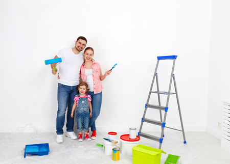 wall paint: happy family mother father and child daughter are doing repairs paint wall at home