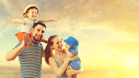 family with baby: happy family of father, mother and two children, baby son and daughter on  the beach at sunset Stock Photo