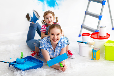 happy family mother and child daughter making repairs, paint the wall at home