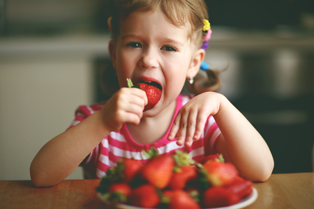 preschooler: happy child girl eats strawberries in the summer home kitchen