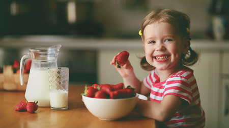 happy child girl eats strawberries in the summer home kitchen