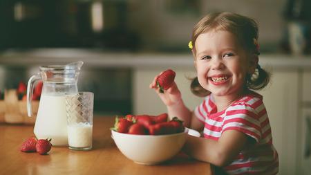 glückliches Kind Mädchen isst Erdbeeren im Sommer Küche zu Hause