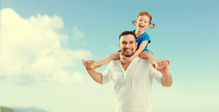 happy family father day. father and child daughter playing and having fun in sky
