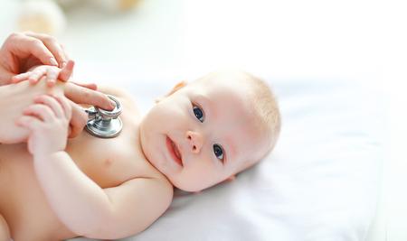 de Doctor kinderarts stethoscoop luisteren aan baby