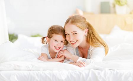 madre e hija familia feliz niño jugando y riendo en la cama en su casa
