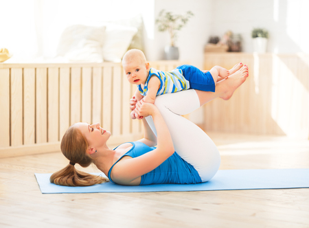 strenuous: sports mother is engaged in fitness and yoga with a baby at home
