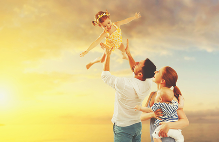 parents with baby: happy family of father, mother and two children, baby son and daughter on  the beach at sunset Stock Photo