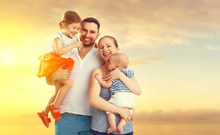 家族: 父、母と 2 人の子供、赤ちゃんの息子と夕日の浜辺の娘の幸せな家庭 写真素材