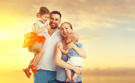 family: família feliz de pai, mãe e dois filhos, filho do bebê e filha na praia ao pôr do sol