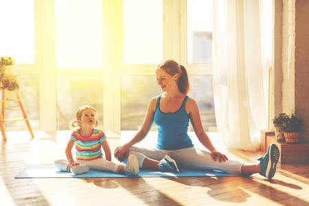 familie moeder en kind dochter houden zich bezig met fitness, yoga, oefening thuis