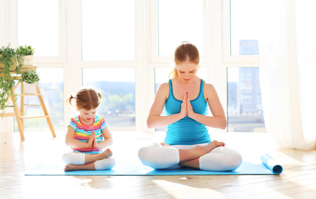 family mother and child daughter are engaged in meditation and yoga, exercise at home Stok Fotoğraf - 59925308