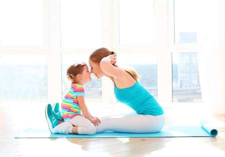 family mother and child daughter are engaged in fitness, yoga, exercise at home Stok Fotoğraf - 57835739