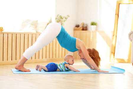 sports mother is engaged in fitness and yoga with a baby at home