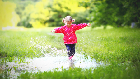 puddle: happy child girl running and jumping in puddles after rain in summer