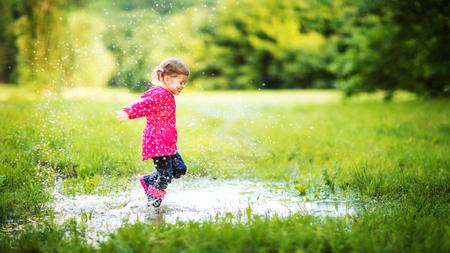 幸せな子供の女の子を実行していると、夏の雨上がりの水たまりにジャンプ