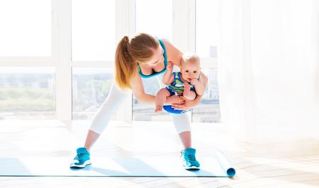 madre y bebe: madre deportes se dedica a la aptitud y el yoga con un bebé en casa