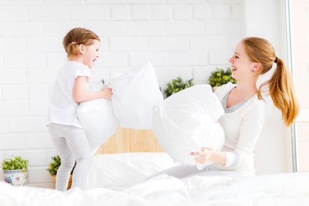 happy family mother and child daughter playing on bed and pillow fight Foto de archivo