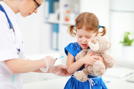 needle syringe infection: Doctor holds an injection vaccination the child