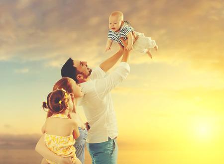 父、母と 2 人の子供、赤ちゃんの息子と夕日の浜辺の娘の幸せな家庭