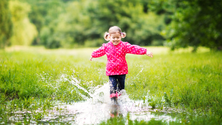 happy child girl running and jumping in puddles after rain in summer Banco de Imagens - 60010189