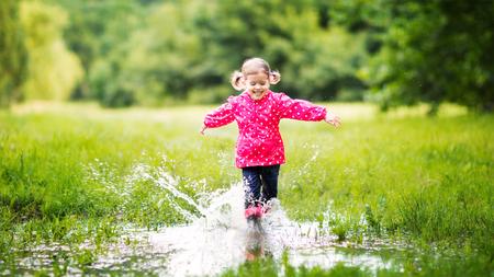 botas de lluvia: niña feliz niño correr y saltar en los charcos después de la lluvia en verano