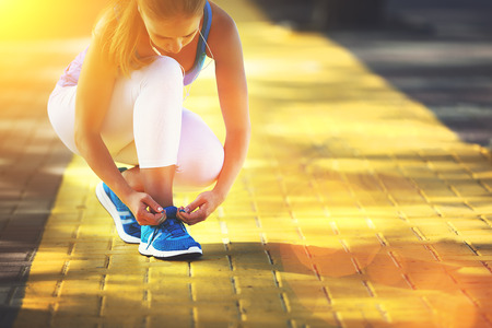 shoelaces: the woman athlete runner run and tying shoelaces