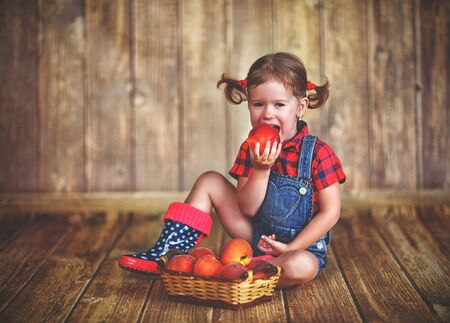 happy child girl with a basket of peaches on a wooden background