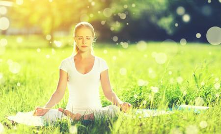 自然の夏に瞑想と緑の芝生でヨガを楽しんでいる若い女性
