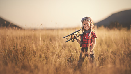 happy child dreams of traveling and playing with an airplane pilot aviator in outdoor in the summer Stok Fotoğraf