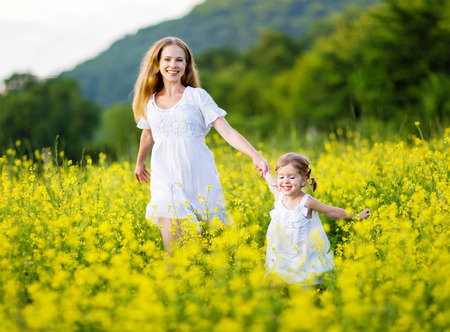 happy family, mother and child girl little daughter playing and running  on the meadow with yellow flowers Stok Fotoğraf - 60130870