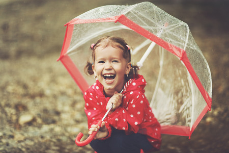 happy child girl laughing with an umbrella in the rain