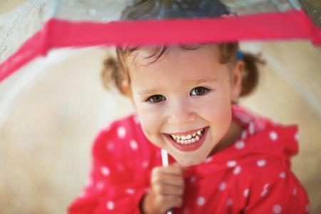 gelukkig kind meisje lachen met een paraplu in de regen Stockfoto
