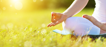 hand position: hand of a woman meditating in lotus position practicing yoga in summer Stock Photo