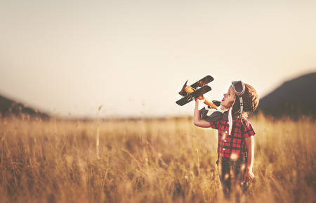 gelukkig kind dromen van het reizen en het spelen met een vliegtuig piloot vliegenier in openlucht in de zomer