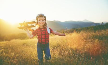 happy child dreams of traveling and playing with an airplane pilot aviator in outdoor in the summer Archivio Fotografico