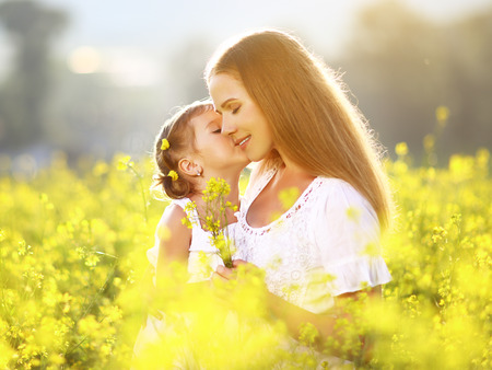 Happy family on a summer meadow. little girl child daughter hugging and kissing mother Standard-Bild
