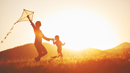 happy family mother and child run on meadow with a kite in the summer on the nature Archivio Fotografico
