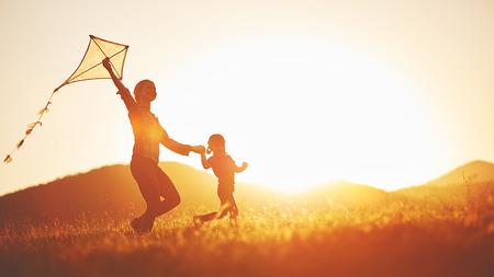 glückliche Familie Mutter und Kind auf der Wiese mit einem Drachen im Sommer auf der Natur laufen Lizenzfreie Bilder