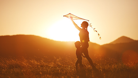 woman flying: happy family mother and child run on meadow with a kite in the summer on the nature Stock Photo
