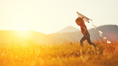 happy child girl with a kite running on meadow in summer in nature