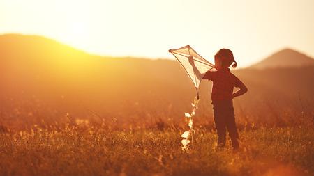 自然の中の夏の草原でカイトと幸せな子供女の子 写真素材