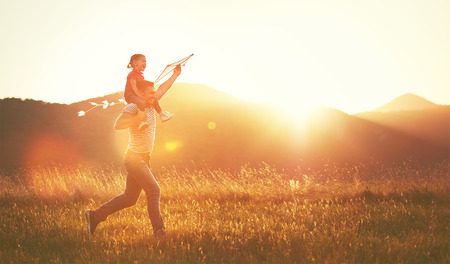 hija: feliz padre de familia y el niño se ejecutan en prado con una cometa en el verano en la naturaleza