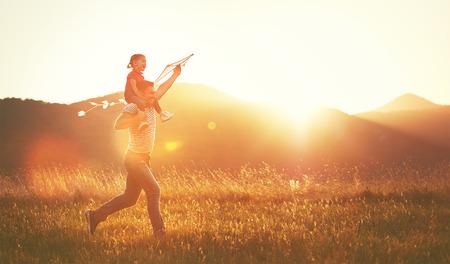 gelukkig gezin vader en kind lopen op de weide met een vlieger in de zomer op de aard