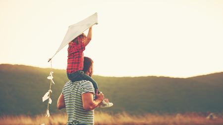 hombros: feliz padre de familia y el niño en prado con una cometa en el verano en la naturaleza
