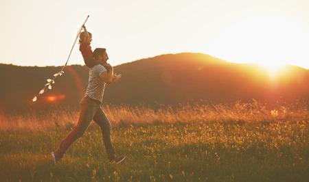 hombros: feliz padre de familia y el niño se ejecutan en prado con una cometa en el verano en la naturaleza