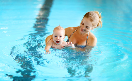 healthy family mother teaching baby swimming pool 스톡 콘텐츠