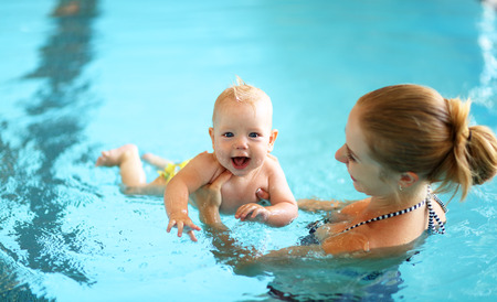 healthy family mother teaching baby swimming pool Banco de Imagens