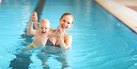 healthy family mother teaching baby swimming pool Reklamní fotografie